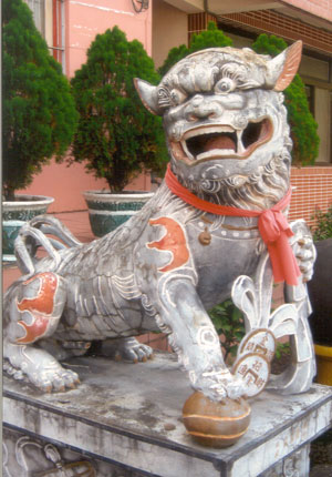 A fierce lion in front of a Buddhist Temple.